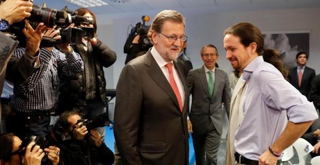 Pablo Iglesias y Mariano Rajoy se saludan en el acto en el que han coincidido en la agencia EFE. /EFE