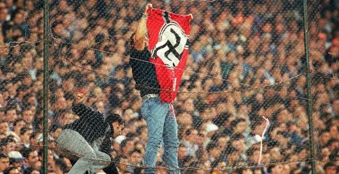 Un hombre coloca una bandera nazi en el Santiago Bernabéu durante un Real Madrid-Barcelona de 1997. - AFP