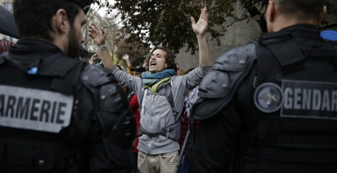 Gendarmes franceses frente a los manifestantes del movimiento Nuit Debout en una concentración frente al Museo del Hombre de Par´si, contra la reforma laboral impulsada por el Gobierno de Hollande. AFP/ KENZO TRIBOUILLARD