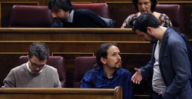 El diputado de IU, Alberto Garzón, conversa con el líder de Podemos, Pablo Iglesias, durante el pleno del Congreso. EFE/Kiko Huesca