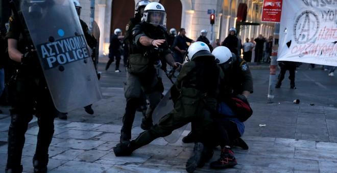 Policías griegos se abalanzan sobre un manifestante. /REUTERS