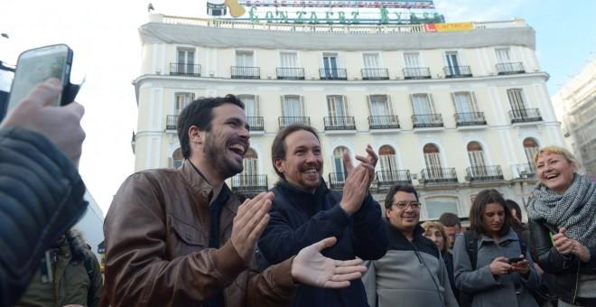 Alberto Garzón, líder de Izquierda Unida, y Pablo Iglesias, secretario general de Podemos, escenifican su acuerdo electoral en la Puerta del Sol de Madrid. PODEMOS