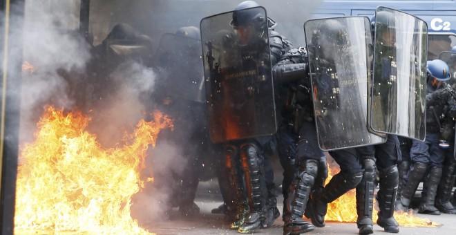Gendarmes franceses, entre llamas provocadas por un grupo de encapuchados en París, durante las protestas contra la reforma laboral.- REUTERS
