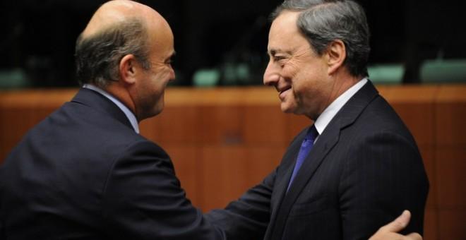 El ministro de Economía, Luis de Guindos, saluda al presidente del BCE, Mario Draghi, en una reunión del Eurogrupo en Bruselas. AFP/ JOHN THYS