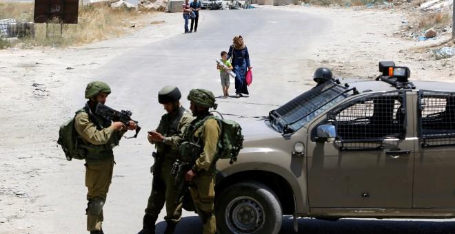 Soldados israelíes vigilan la entrada a la ciudad palestina de Yatta. REUTERS/Mussa Qawasma