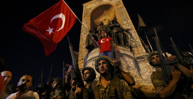 Militares turcos hacen guardia en la Plaza Taksim de turquía mientras ciudadanos turcos ondean la bandera del país. REUTERS/Murad Sezer
