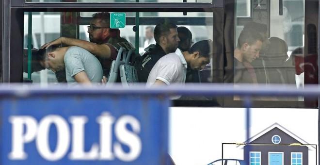 Policías turcos escoltan en un bus a soldados detenidos tras el golpe. - EFE