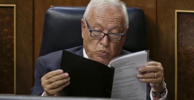 El ministro de Asuntos Exteriores, José Manuel García-Margallo siguen desde su escaño la intervención del presidente del Gobierno en funciones, Mariano Rajoy, durante la primera jornada del debate de investidura a la que se somete, esta tarde en el Congre