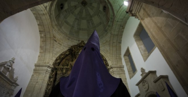 "A hooded penitent of the ""Numeraria del Rosario"" brotherhood waits for the start of the Santo Entierro procession at the San Domingos de Bonaval church, during Holy Week in Santiago de Compostela, northwestern Spain, on March 25, 2016. Christian believers"