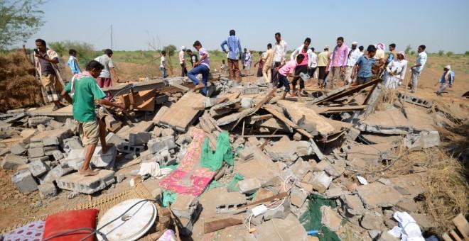 Un grupo de personas permanece de pie junto a una casa destruida por los ataques aéreos de la coalición árabe en Yemen. REUTERS/Abduljabbar Zeyad