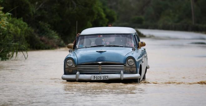 Un coche circula por una carretera inundada de Guantánamo tras el paso del huracán Matthew. / ALEXANDRE MENEGHINI (REUTERS)