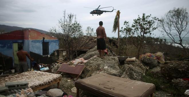 Un hombre observa un helicóptero en Cajobabo (Cuba) tras el paso del huracán Matthew. / ALEXANDRE MENEGHINI (REUTERS)
