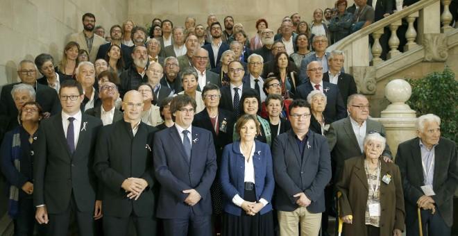 El presidente de la Generalitat Carles Puigdemont y la presidenta del Parlament de Cataluña Carme Forcadell junto a otros diputados, posan con familiares y víctimas del franquismo tras la sesión que ha acordado por unanimidad tramitar la proposición de le