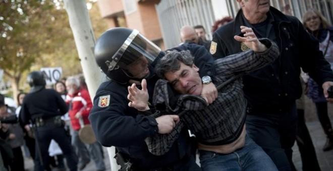 Un agente detiene a un ciudadano que participaba en una manifestación. / EFE
