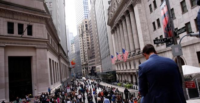 Un hombre sentado sobre un muro de mármol en frente del New York Stock Exchange, EEUU. / REUTERS