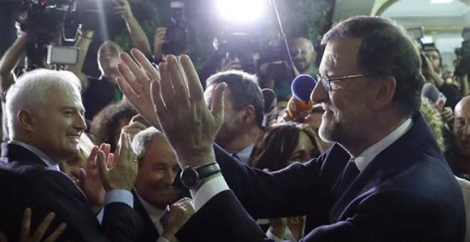 El líder del PP y presidente del Gobierno en funciones, Mariano Rajoy (d) a su salida del congreso tras ser investido hoy presidente del Gobierno por mayoría simple al conseguir 170 votos a favor, del PP, Ciudadanos, CC, Foro y UPN, 111 en contra y 68 ab