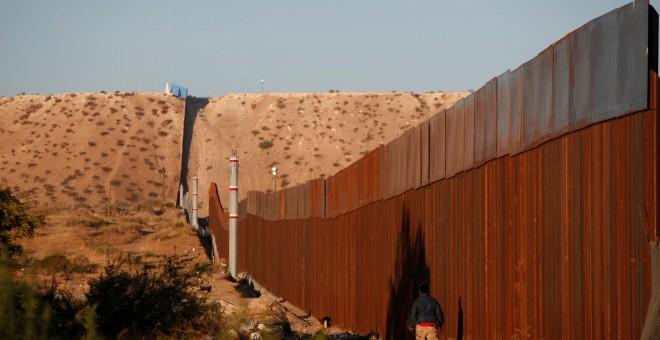 Un hombre pasa por una sección del muro que separa EEUU de México, cerca de Ciudad Juarez. REUTERS/Jose Luis Gonzalez