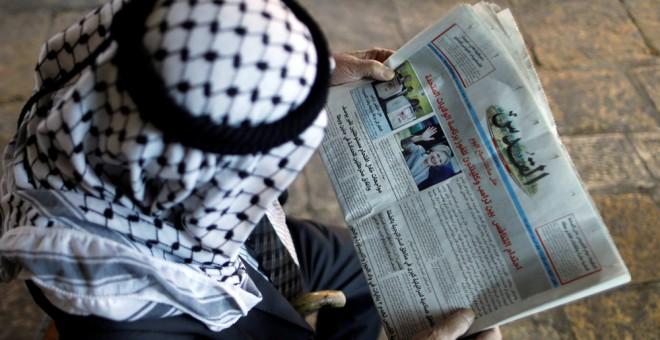 Un palestino lee en el diario 'Al-Quds' la noticia de las elecciones en EEUU. REUTERS/Ammar Awad