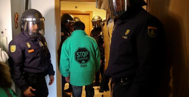 Un activista antidesahucios abandona entre agentes de la policía el domicilio de Jose Antonio Rojas Marcos y Jessica Guabala de la Cruz, en Parla. REUTERS/Andrea Comas