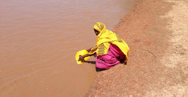 Mujer recogiendo agua en un río en Burkina Faso. / AUARA