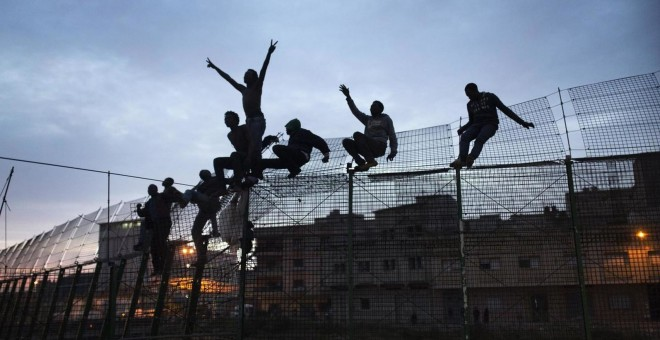 Inmigrantes intentan saltar la valla de Melilla. Archivo REUTERS (2014)