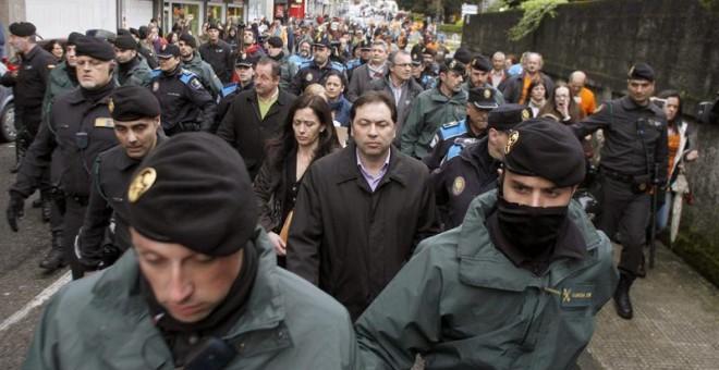 Concejales de Ponteareas salen escoltados del pleno por la policía tras una protesta de los preferentistas. / EFE