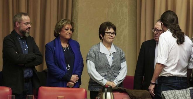 El líder de Podemos, Pablo Iglesias (d), saluda a miembros de la Asociación de Familiares de víctimas del accidente del Yak42, antes de la comparencia comparecer a petición propia en el Congreso, para informar del dictamen del Consejo de Estado sobre el a