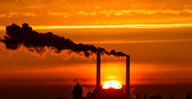 e levanta detrás de las chimeneas de billowing de la central eléctrica en Berlín/REUTERS