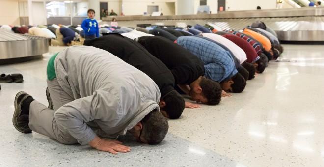 Varias personas rezan como los musulmanes en el aeropuerto internacional de Dallas como parte de las protestas que se están produciendo en todo EEUU contra el veto de Trump a los inmigrantes.  REUTERS / Laura Buckman