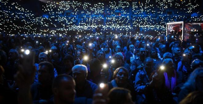 Assistents al concert en favor de l'acollida als refugiats il·luminen amb els seus mòbils
