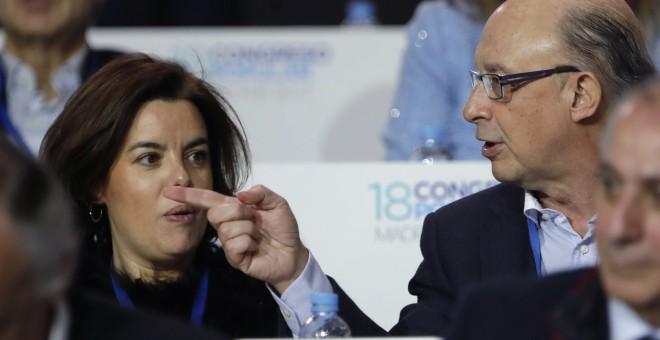 El ministro de Hacienda, Cristóbal Montoro, junto a la  vicepresidenta del Gobierno, Soraya Sáenz de Santamaría, durante el el XVIII Congreso Nacional del PP en la Caja Mágica de Madrid. EFE/JuanJo Martín