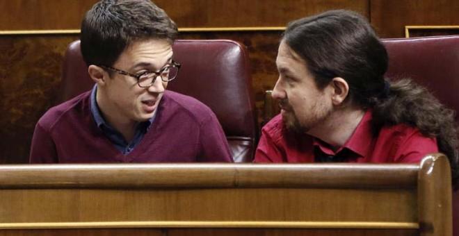 El líder de Podemos, Pablo Iglesias (d), conversa con el portavoz parlamentario de esta formación, Íñigo Errejón, en el hemiciclo del Congreso. | FERNANDO ALVARADO (EFE)