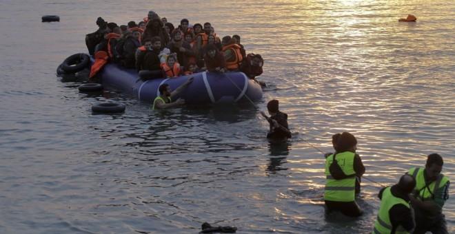 Voluntarios de una ONG ayudan a refugiados y migrantes que llegan en una lancha neumática a la costa de Mytilini, en la isla de Lesbos (Orestis Panagiotou / EFE)