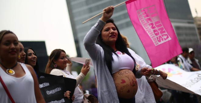 A pregnant woman holds a flag as she takes part in a march on International Women's Day in Mexico City, Mexico, March 8, 2017. The flag reads, 'Not one (woman) less. Alive we want us'. REUTERS/Edgard Garrido