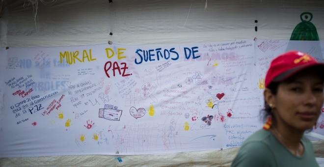 Una guerrillera de las FARC pasa delante de un mural en favor de los acuerdos de paz con el Gobierno colombiano, en la zona veredal de transición de La Elvira, en el Cauca.- JAIRO VARGAS