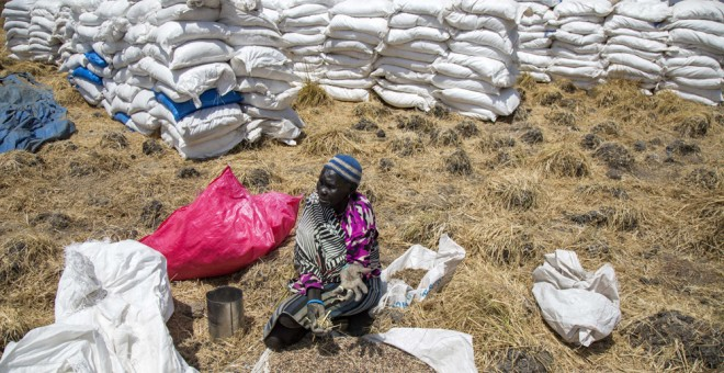 Una mujer recoge granos dejados en el suelo después de una distribución de alimentos en Sudán del Sur. AFP/Albert González Farran