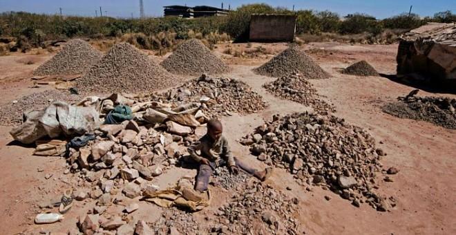 Un niño rompe rocas extraídas de una minería de cobalto en una mina de cobre y un pozo de cobalto en Lubumbashi el 23 de mayo de 2016. El precio del cobre ha caído fuertemente, afectando directamente a los trabajadores de la ciudad. JUNIOR KANNAH / AFP