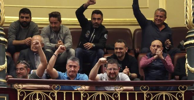 Un grupo de estibadores saludan desde la tribuna de invitados del Congreso donde se debatia el real decreto ley de reforma de la estiba. EFE/Ballesteros