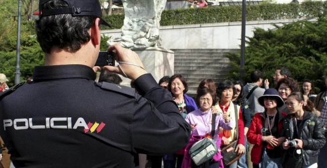 Un policía toma una foto a un grupo de turistas japoneses en Madrid.-EFE