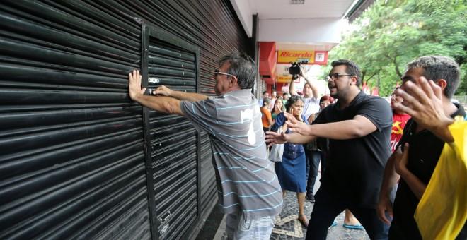 Un hombre intenta romper la puerta de una tienda durante una protesta en la huelga general de este viernes en Brasil REUTERS / Paulo Whitaker