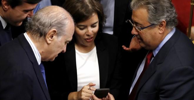 La vicepresidenta del Gobierno, Sorya Sáenz de Santamaría, conversa con el ministro del Interior, Juan Ignacio Zoido (d), y los diputados del PP Jorge Fernández Díaz (i) y José Luis Ayllón (2-i), durante un receso en el debate de las enmiendas a la totali