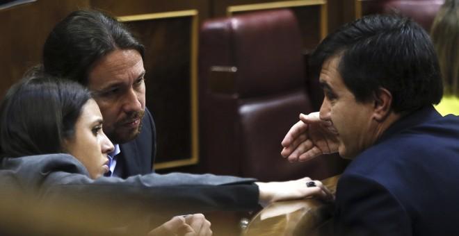 El diputado del PP y secretario de Estado de Relaciones con las Cortes, José Luis Ayllón, conversa con el el líder de Podemos, Pablo Iglesias, y la portavoz del partido, Irene Montero, durante el debate de las enmiendas a la totalidad de los presupuestos