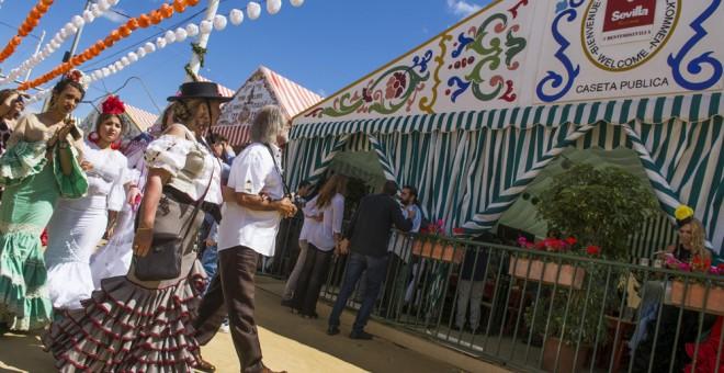 Unas personas llegan a la caseta que el Ayuntamiento sevillano ha dispuesto abierta para los turistas que visitan la Feria de Abril, ya que la mayoría son privadas. EFE/ Raúl Caro
