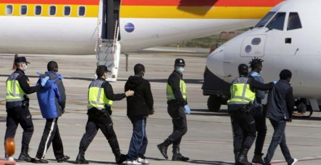 La Policía traslada hasta el avión a un grupo de inmigrantes que va a deportar desde Melilla.- EFE / ARCHIVO