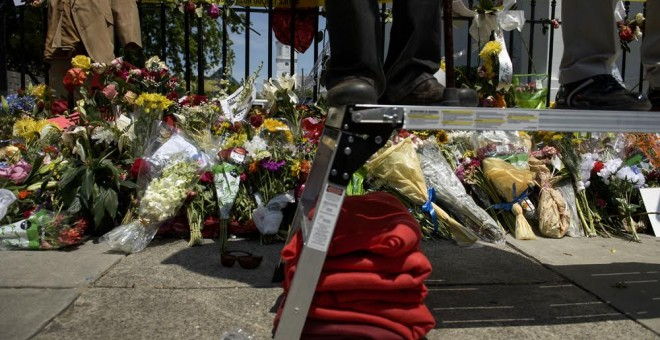 Miles de personas en duelo rezan fuera de la Iglesia Emanuel AME en Charleston el 30 de junio de 2015. Portando flores rojas y blancas, acudieron a la vigilia por el asesinato de nueve afroamericanos a manso de un supremacista blanco. AFP PHOTO/BRENDAN SM