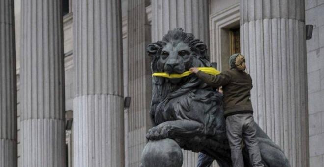 Una activista de Greenpeace amordaza los leones del Congreso de los Diputados. - Foto: EFE
