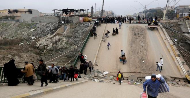 Personas desplazadas que huyen de los militantes del Estado Islámico cruzan el puente del barrio de Al-Muthanna en Mosul REUTERS/Ahmed Saad/File photo