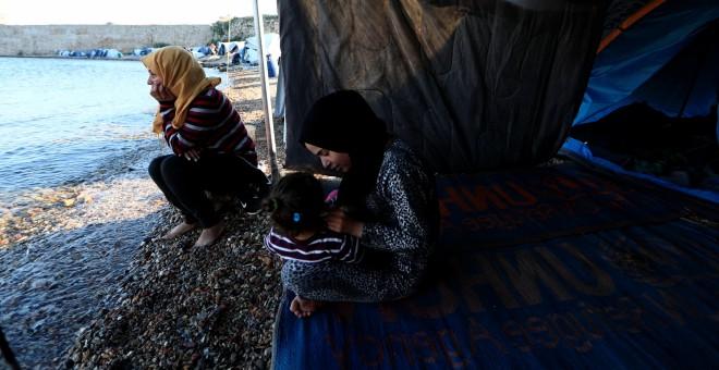 Faten (i), procedente de Siria, se sienta a la orilla del mar junto a su nuera, cerca de su tienda en el campo de refugiados de Souda, en la isla de Chios. 'Está tardando demasiado. Esta lentitud para traer a toda la familia me asusta', dice Faten. 'No te