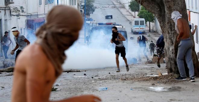 Manifestantes encapuchados lanzan piedras a la Policía antidisturbios durante la multitudinaria protesta en Alhucemas, Marruecos, el pasado 20 de julio.- REUTERS