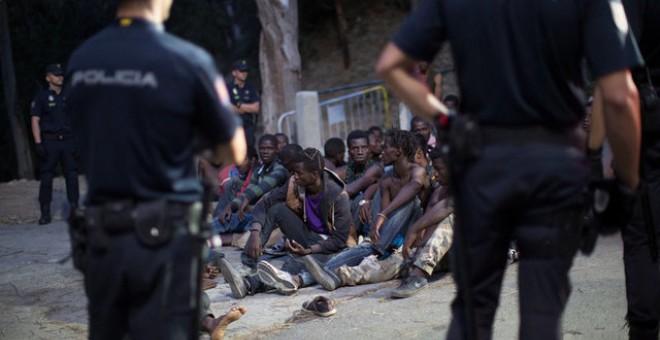 La Policía frente al grupo de migrantes después de saltar la valla de Ceuta / REUTERS